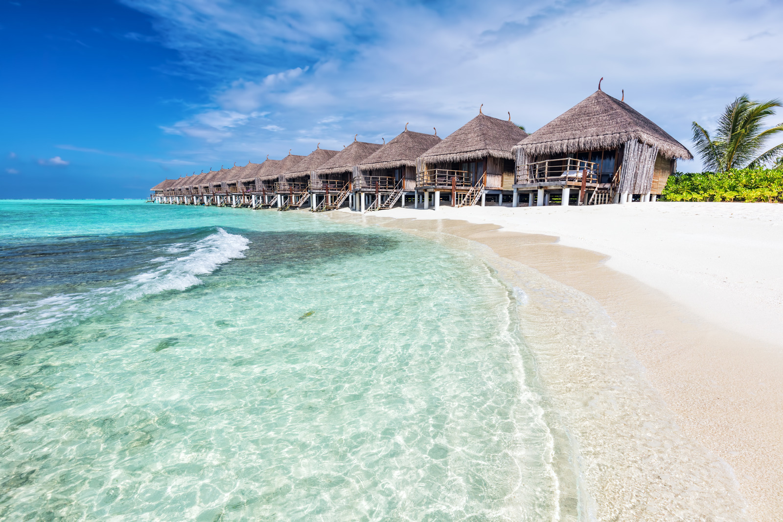 Water villas in a row by the seashore on Maldives. Tropical resort with an ocean view. Honeymoon destinations.